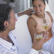 Couple drinking wine on couch — Stock Photo
