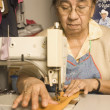 Stock Photo: Senior womusing sewing machine