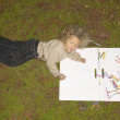 Young girl drawing outside — Stock Photo