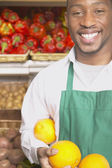 Male African American supermarket worker with fruit — Stock Photo