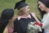 Older graduate receiving praise from family — Stock Photo