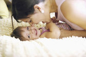 Mother playing with toddler on bed — Stock Photo