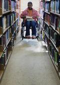 αρσενικό φοιτητής σε αναπηρική καρέκλα σε βιβλιοθήκη — Φωτογραφία Αρχείου