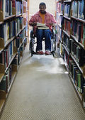Male college student in wheelchair at library — Stok fotoğraf