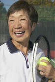 Senior Asian woman with tennis racket and ball — Stock Photo