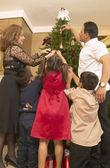 Hispanic family decorating Christmas tree — Stock Photo