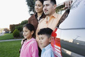 Family standing together beside minivan — Stock Photo
