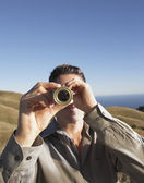 Man using telescope to view distant hills — Stock Photo