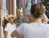Woman taking picture of elderly couple posing — Stock Photo