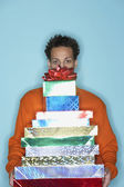 Young man behind stack of gifts — Stock Photo