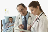 Doctors discussing a patient's medical chart — Stock Photo