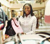 Mulher mostrando designer mala na loja — Fotografia Stock
