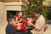 Hispanic siblings shaking Christmas gifts — Stock Photo