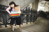 Young woman carrying notebooks upstairs — Stock Photo