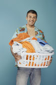Young man holding basket of laundry — Stock Photo