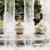 бизнесмен, стоял позади фонтана — Стоковое фото