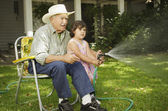 Elderly man sitting in lawn chair helping granddaughter spray water — Stock Photo
