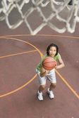 Teenage girl shooting hoops — Stock Photo