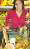 Asian woman in produce section of grocery store — ストック写真
