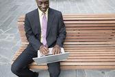 Zakenman zitten buiten met behulp van laptop — Stockfoto