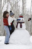 Mother and son building snowman — Stock Photo