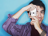Young man taking a picture with a digital camera — Stock Photo