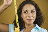 Woman looking sideways holding tape measure — Stock Photo
