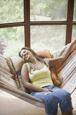 Young woman reclining on swing — Stock Photo