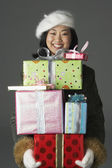 Young woman with stack of gifts — ストック写真