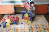 Boy playing with cardboard blocks — Stock Photo