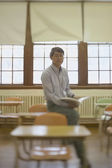 Male teacher sitting in classroom — Stock Photo