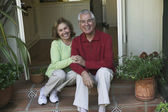 Senior Hispanic couple sitting on steps — Stock Photo