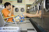 Man with lawn chair and binoculars at laundromat — Stock Photo