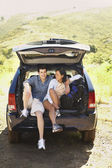 Couple posing inside SUV hatch — 图库照片