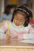 Chica escribiendo en mesa de salón de clases — Foto de Stock