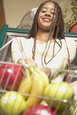 African American woman with groceries in basket — Stock Photo