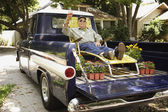 Portrait of elderly man in lounge chair and sunglasses relaxing in back of pickup truck — Stockfoto