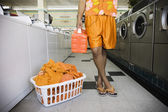 Low section of man with soap and laundry in laundromat — Stock Photo