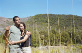 Couple with hiking stick hugging outdoors — Stock Photo