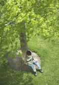 Overhead view of boy reading under tree — Stock Photo