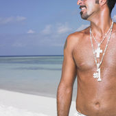 Man's chest with necklaces at beach — Stock Photo