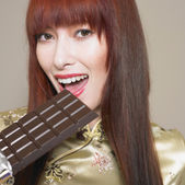 Portrait of woman eating chocolate bar — Stock Photo