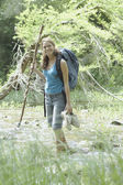 Young woman wading in forest stream — Stock Photo