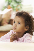 Young African American girl praying at bedside — Stock Photo