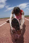 Female track runner stretching her legs — Stock Photo