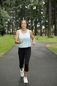 Portrait of woman jogging through park — Stock Photo