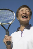 Close up of senior Asian woman with tennis racket — Stock Photo