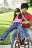 Girl and young man on bicycle — Stock Photo
