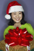 Young woman carrying gift with bow — Stock Photo