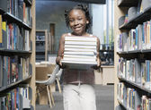 Girl holding books in library — Stock Photo